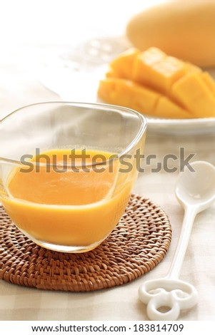 A glass of orange juice sitting on a coaster with a spoon. - stock photo
