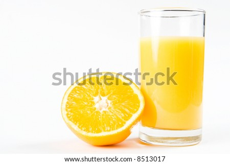 A glass of orange juice with half an orange