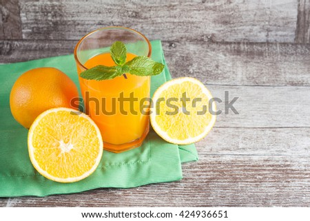 A glass of orange juice with mint and fresh fruits on wooden background - stock photo