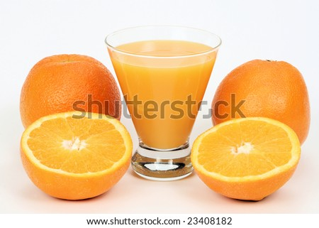 A glass of orange juice with sliced oranges around it