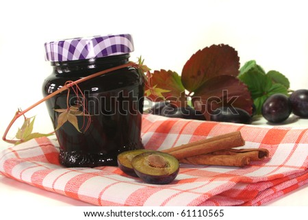 a glass of plum jam with fresh ingredients