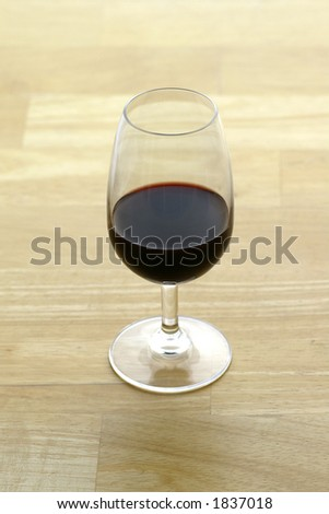 A glass of Port (Vinho do Porto) sitting on a butcher block surface