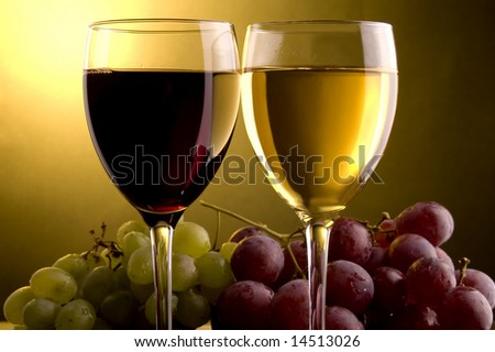 a glass of red and white wine and red and green grape