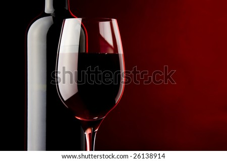 a glass of red wine and a bottle - stock photo