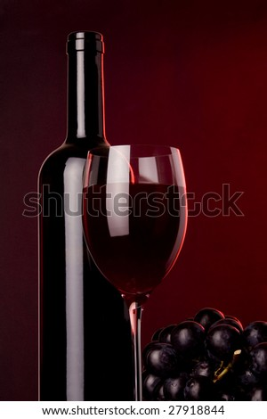 a glass of red wine and a bottle and grape