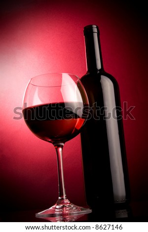 a glass of red wine and a bottle in the spotlights