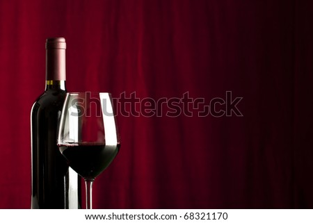 a glass of red wine and a bottle on red background