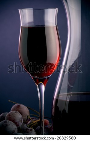 a glass of red wine and a jug and  grape