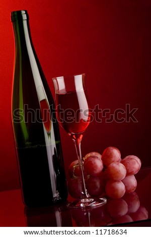 a glass of red wine and bottle and grape