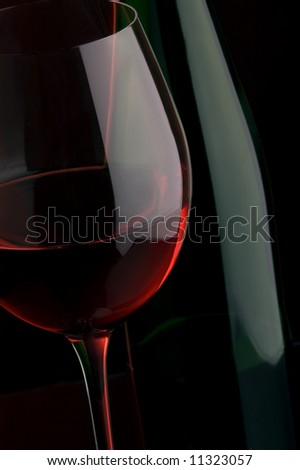 a glass of red wine and bottle details