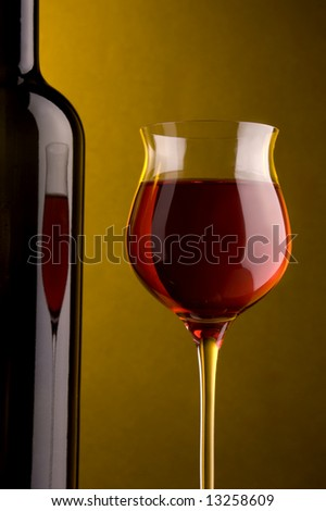a glass of red wine and bottle`s detail