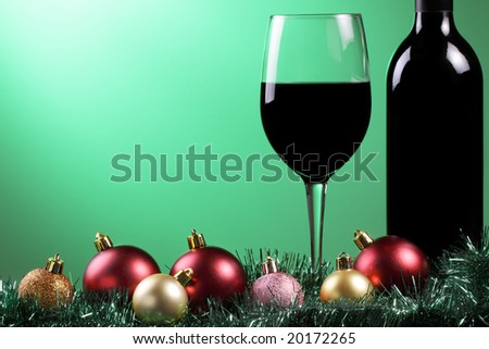 A glass of red wine and bottle with xmas decorations on a graduated green background. - stock photo
