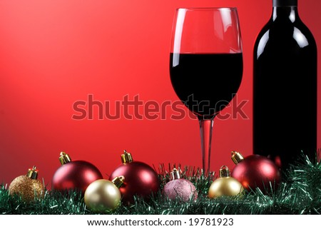A glass of red wine and bottle with xmas decorations on a graduated red background. - stock photo