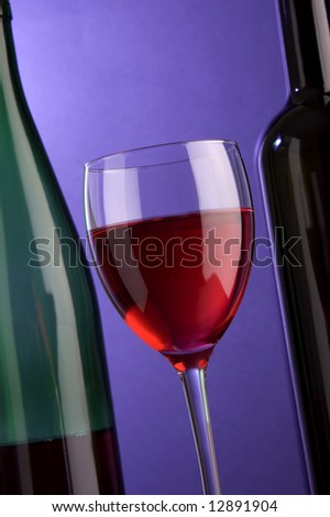 a glass of red wine and bottles