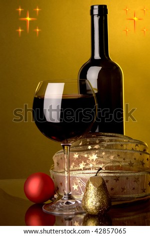 a glass of red wine and christmas decoration - stock photo