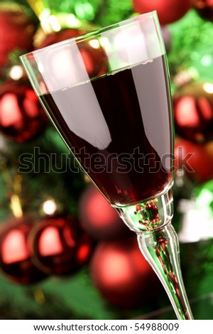 a glass of red wine and Christmas tree at background - stock photo