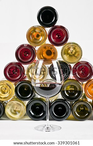 a glass of red wine and wine bottles on background - stock photo