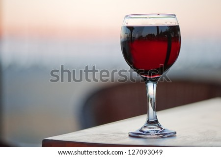 A glass of red wine at sunset. - stock photo