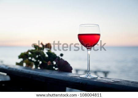A glass of red wine at sunset on terrace - stock photo
