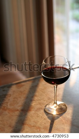 A glass of red wine brightly lit by the sun.