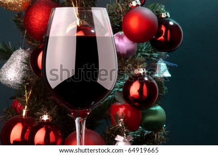 a glass of red wine detail and Christmas tree at background - stock photo