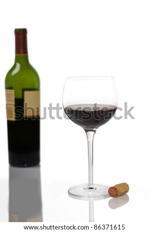 A glass of red wine in the foreground with a cork beside it and an out of focus bottle of red wine in the background, all with reflections. - stock photo