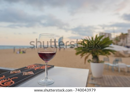 A glass of red wine on a bar overlooking the beach in Barcelona, Spain at sunset. Concept of a relaxing, blissful vacation.