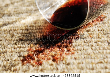 A glass of red wine spilt on a pure wool carpet. - stock photo