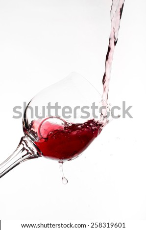a glass of red wine which is poured on a white background