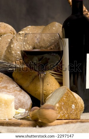 A glass of red wine with an assortment of breads and cheeses.