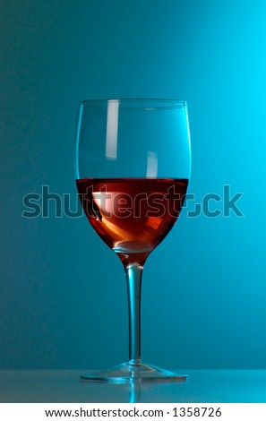 A glass of red wine with blue background - stock photo