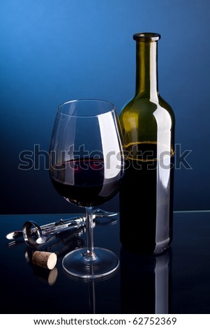 A glass of red wine with bottles on a blue background