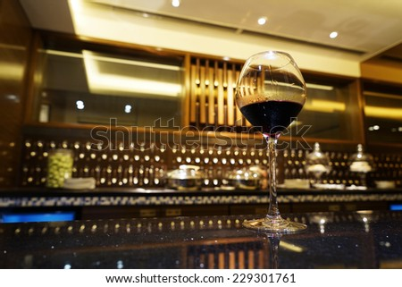 A glass of red wine with modern living room background. - stock photo