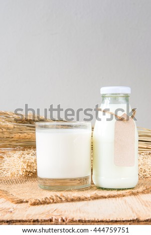A glass of rustic milk and bottle glass of rustic milk and ear of rice dry on a wood table on white background, tasty, nutritious and healthy dairy products - stock photo