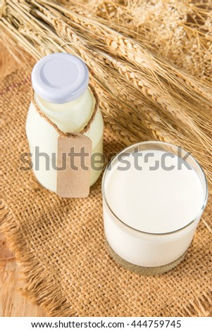A glass of rustic milk and bottle glass of rustic milk and ear of rice dry on a wood table, tasty, nutritious and healthy dairy products - stock photo