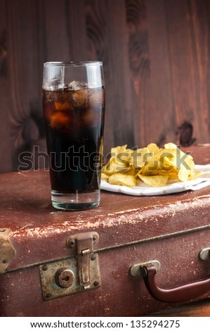 A glass of soda with chips on the dark background - stock photo