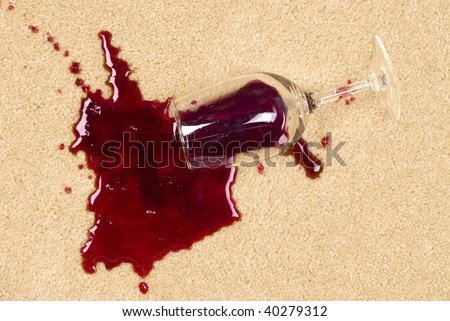 A glass of spilled wine on brand new carpet is sure to leave a stain. - stock photo