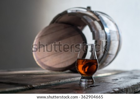 A glass of spirits in the oak barrel - stock photo