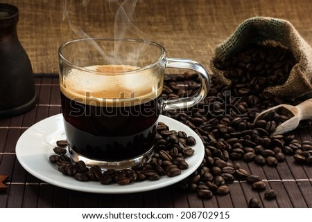 A glass of steaming hot fresh coffee on a white plate with coffee beans - stock photo