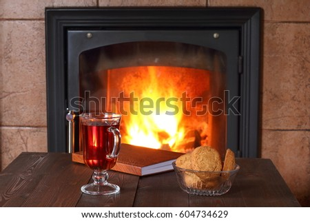 A glass of tea biscuits and book are on the table in front of the fireplace.