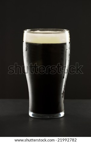 A glass of the famous irish black stout beer against a dark background