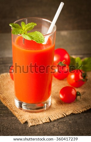 a Glass of tomato juice, mint and slices of tomato on wooden background. Healthy drink concept. Vitamines and diet. Shake and smoothie.