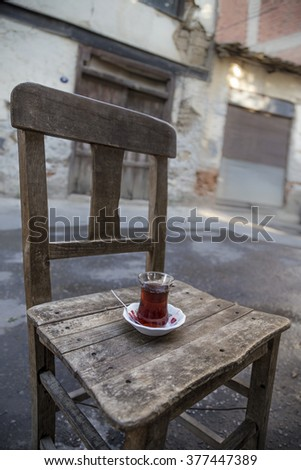 a glass of turkish tea on a wooden chair