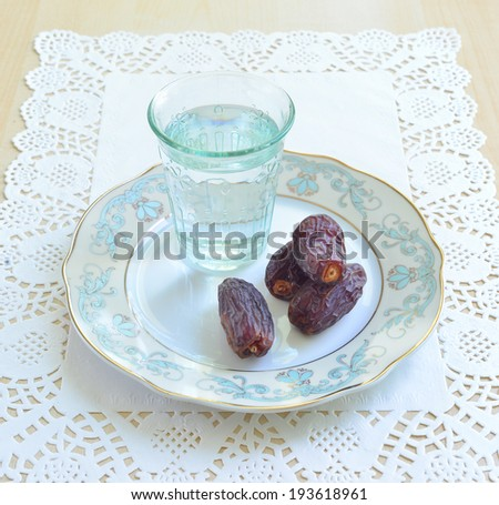 A glass of water and dates- a food to break fast during holy month of Ramadan - stock photo