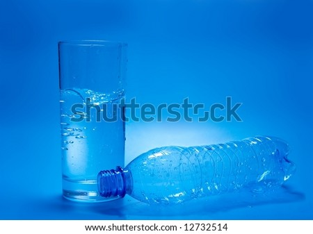 A glass of water and empty bottle - stock photo