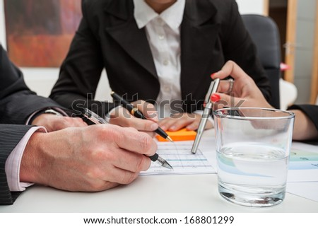 A glass of water and hands of businessmen