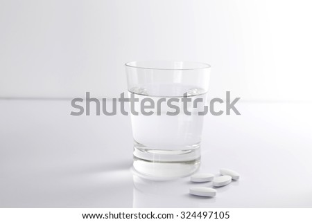A glass of water and pills on a white background  - stock photo