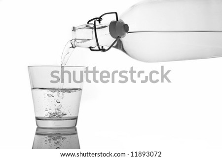 A glass of water being served from a bottle. Isolation with clipping path. - stock photo