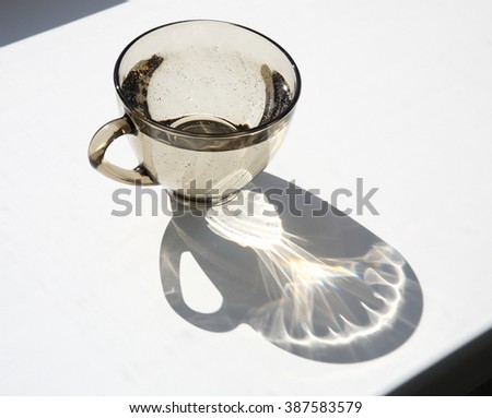 A glass of water on the windowsill in the sunlight. - stock photo