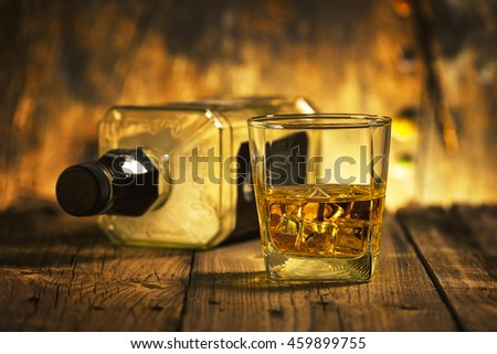 A Glass of whiskey and empty Bottle of whiskey on a wooden background - stock photo
